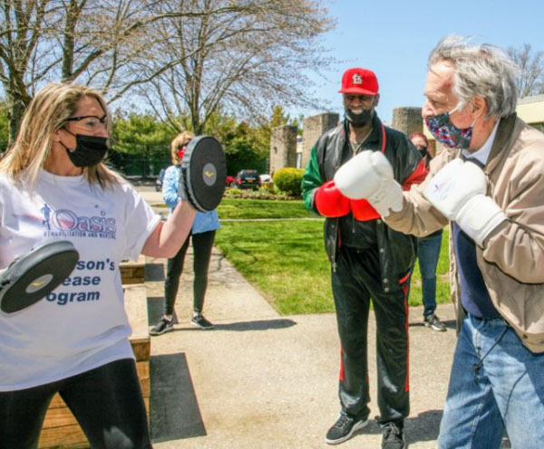 Oasis Parkinson's Disease Program Coordinator Shari Gessner, left, instructs the class while Hall of Fame boxer Michael Spinks watches.